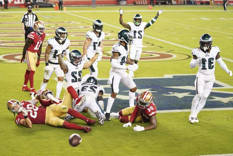 a group of baseball players playing a football game: Philadelphia Eagles players celebrate after an incomplete pass by the San Francisco 49ers during the fourth quarter at Levi's Stadium.