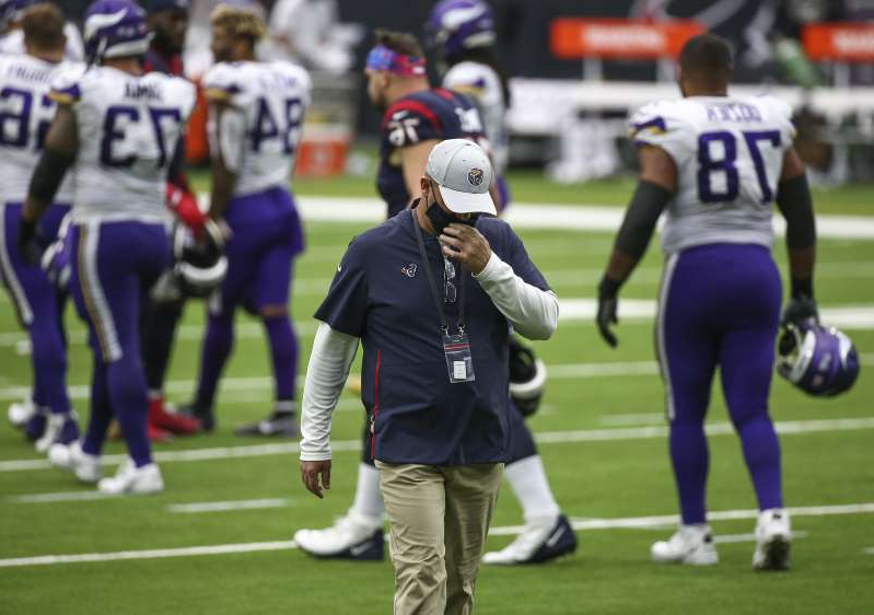 a group of football players playing a football game: Houston Texans head coach Bill O'Brien walks off the field after a loss to the Minnesota Vikings at NRG Stadium.