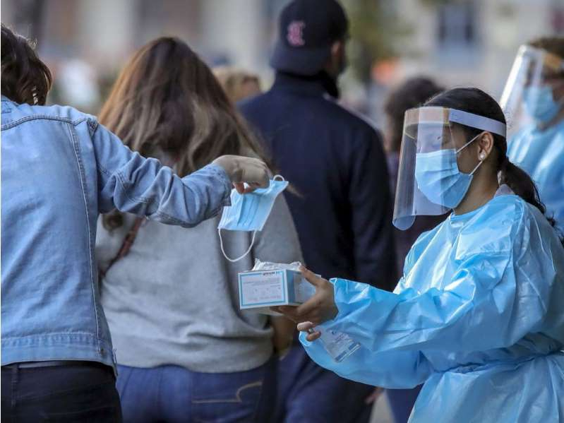 a group of people looking at a phone: A worker from the Park Extension COVID-19 testing centre hands a surgical mask to a woman waiting in line in Montreal Thursday September 24, 2020.
