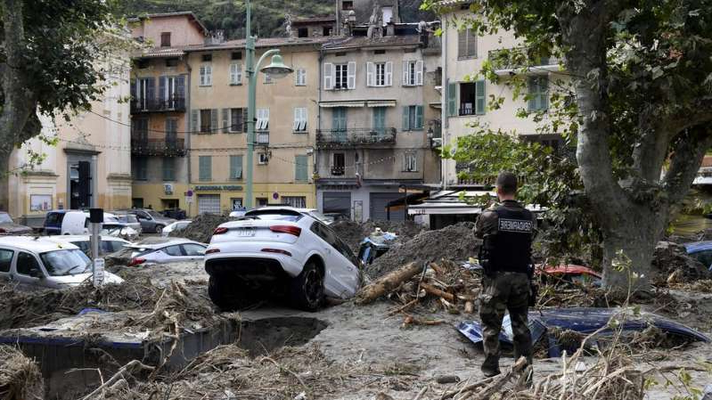 a group of people sitting around a car: Hundreds of people have been evacuated in south-eastern France