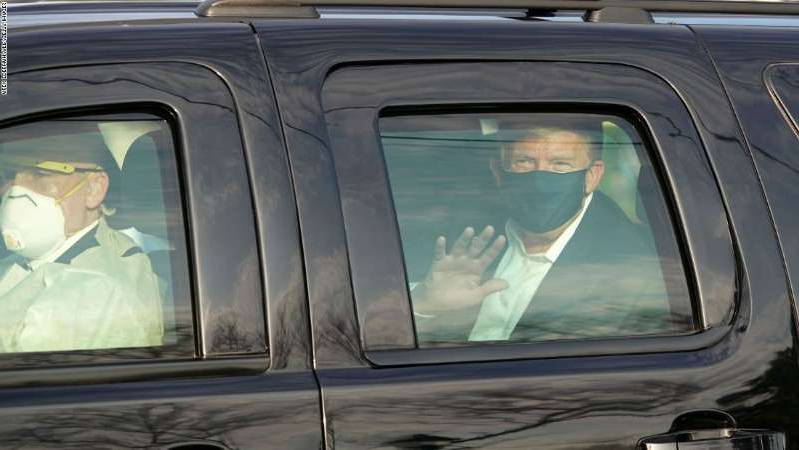 a passenger seat of a car: US President Trump waves from the back of a car in a motorcade outside of Walter Reed Medical Center in Bethesda, Maryland on October 4, 2020.