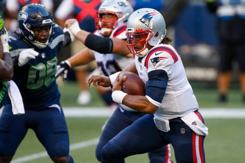 a group of men playing a game of baseball: New England Patriots quarterback Cam Newton (1) rushes against the Seattle Seahawks during the second quarter at CenturyLink Field.
