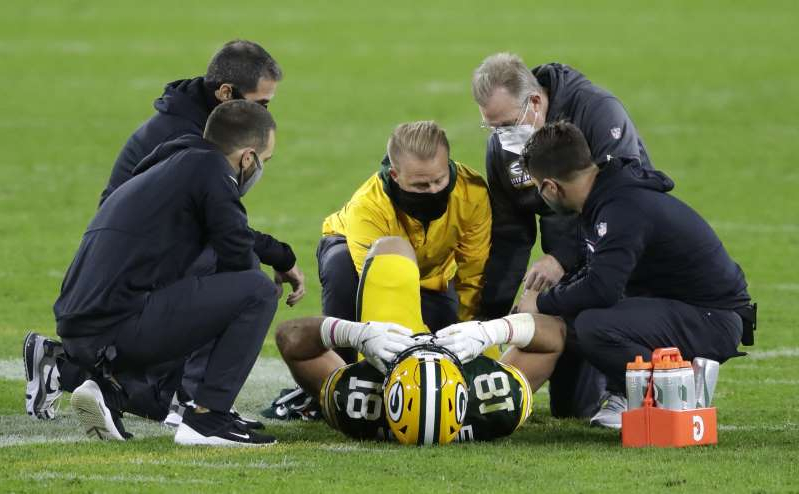 a group of people sitting around a baseball field: Green Bay Packers tight end Josiah Deguara (81) is treated after getting injured against the Atlanta Falcons during their football game Monday, October 5, 2020, at Lambeau Field in Green Bay, Wis.