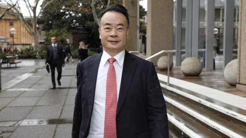 a man wearing a suit and tie standing in front of a building: Dr Chau Chak Wing is suing the ABC for defamation. (AAP: Chris Pavlich)
