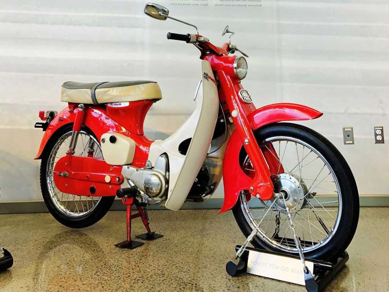 a bicycle is parked next to a motorcycle: The Honda 50 (the Super Cub name was taken) basically started the Honda Motor Company when it came out in 1958, and Honda's built more than 110 million of them since.