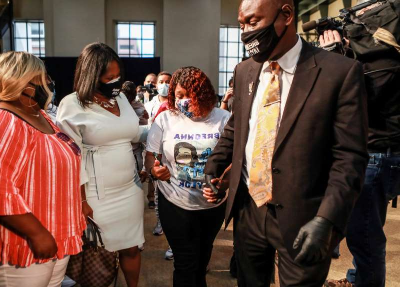 a couple of people that are talking to each other: Attorney Ben Crump holds the hand of Tamika Palmer, the mother of Breonna Taylor, as they leave Metro Hall after the city of Louisville agreed to pay $12 million to the estate of Breonna Taylor. At Palmer's left is attorney Lonita Baker, who also represents Taylor's family. Sept. 15, 2020