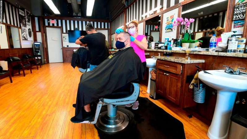 a person sitting on a table: Hairdressers work with customers seated inside for the first time in months in September at Angelo's Barber Shop in downtown Los Angeles.