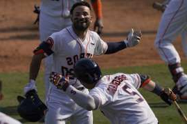 a baseball player holding a bat on a field: Houston Astros' Jose Altuve, top, is congratulated by Alex Bregman after hitting a two-run home run against the Oakland Athletics during the seventh inning of Game 4 of a baseball American League Division Series in Los Angeles, Thursday, Oct. 8, 2020. (AP Photo/Ashley Landis)
