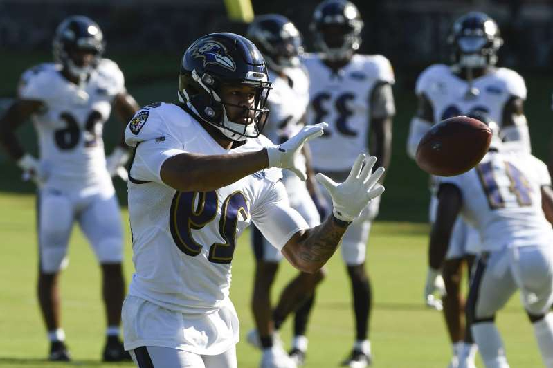 a football player holding a bat on a baseball field: Earl Thomas III (29) remains a free agent following his release by the Ravens.