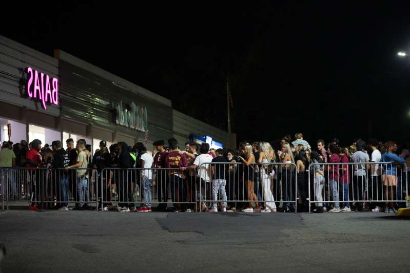 a group of people standing in front of a crowd: A long line forms outside Bajas Beachclub before the doors to the popular nightclub re-open Saturday, Oct. 3, 2020.