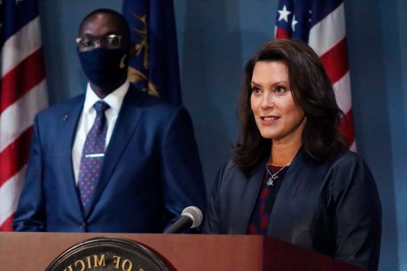 a person wearing a suit and tie: FILE - In this Wednesday, Sept. 2, 2020 file photo provided by the Michigan Office of the Governor, Gov. Gretchen Whitmer addresses the state during a speech in Lansing, Mich. Gov. Whitmer's office said Thursday, Sept. 17, 2020, her requirement that athletes wear masks applies to Big Ten football in Michigan, but a face shield will suffice for players and the administration is open to potentially changing the order. (Michigan Office of the Governor via AP, File)