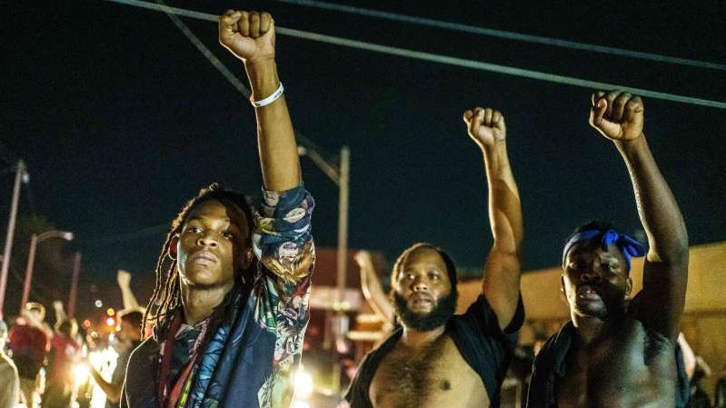 a group of people wearing costumes: Protesters in Kenosha, Wisconsin, on August 26, 2020, raise their fists at a demonstration against the police shooting of Jacob Blake.