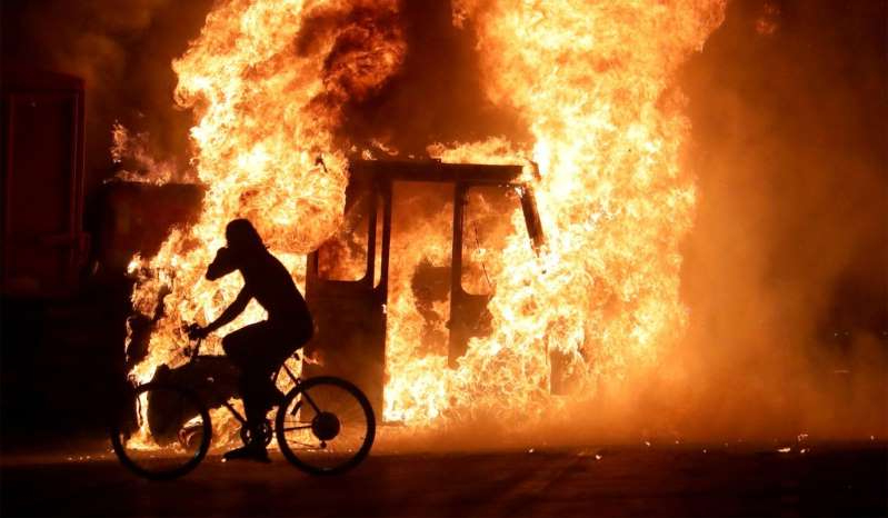 a person riding on the back of a fire: A man on a bike rides past a city truck on fire outside the Kenosha County Courthouse during riots following the police shooting of Jacob Blake, Kenosha, Wis., August 23, 2020.