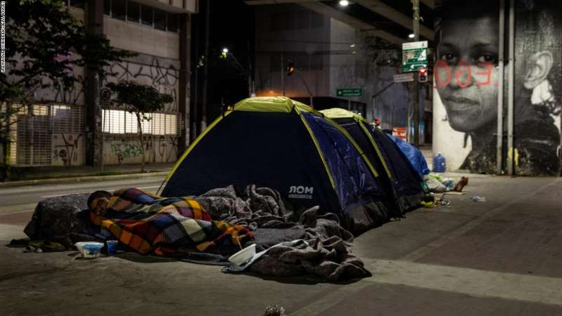 a person sitting in a parking lot: Homeless people sleep in tents on the sidewalk in downtown São Paulo, Brazil, on August 28, 2020. Due to the pandemic, unemployment is rising and the number of people living on the streets has increased considerably.