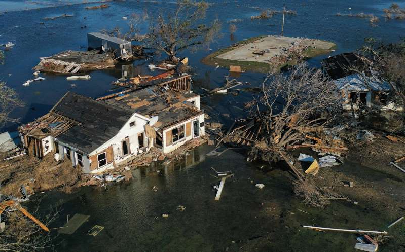 a flock of birds flying over a body of water: An aerial view of flood waters from Hurricane Delta surrounding structures destroyed by Hurricane Laura on October 10 in Creole, Louisiana. Over 400,000 were reported to be without power in Louisiana, Texas and Mississippi, as of Sunday.