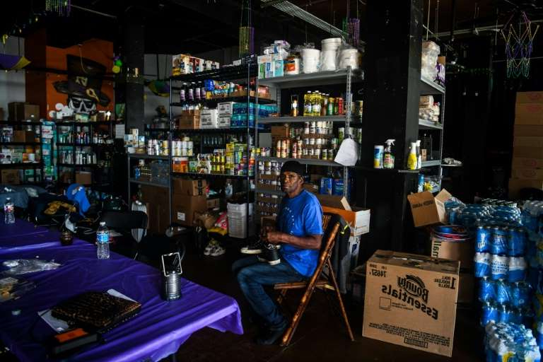 a person sitting at a table in front of a store: Robert Berard sits in a Cajun Navy shelter in Lake Charles, Louisiana on October 10, 2020, one day after Hurricane Delta passed through the area