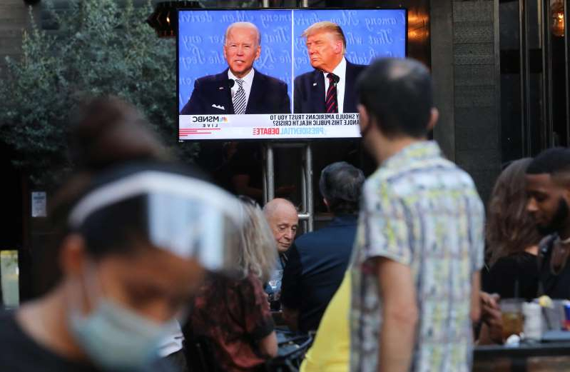 Donald Trump, Joe Biden are posing for a picture: A server wears a face shield and face-covering as people sit to watch a broadcast of the first debate between President Donald Trump and Democratic presidential nominee Joe Biden.