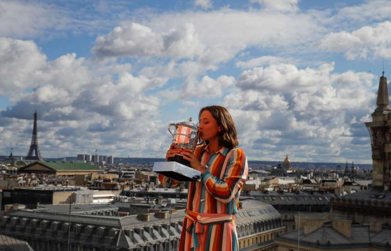 Poland's Iga Swiatek, suddenly becoming a Grand Slam champion at the age of 19, poses with her trophy during a photo call on the rooftop of Galeries Lafayette, Sunday, Oct. 11, 2020, after winning the final match of the French Open tennis tournament against Sofia Kenin of the U.S. at the Roland Garros stadium in Paris, France, Saturday. (AP Photo/Christophe Ena)