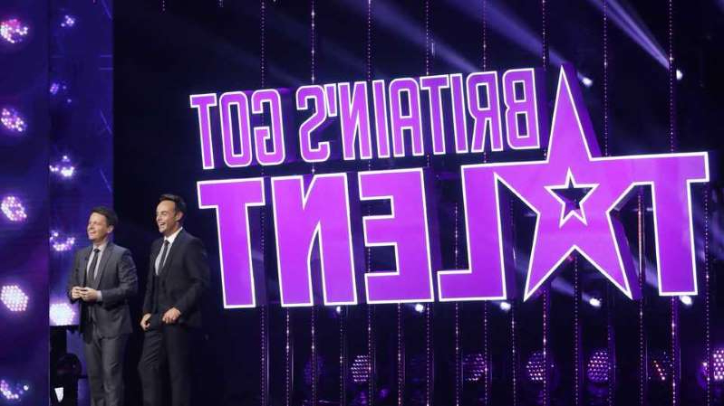 a person standing on a stage in front of a sign: BGT