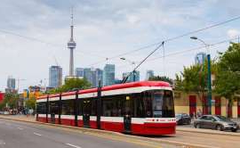 a public transit bus on a city street: A streetcar runs down Toronto's Spadina Ave. in this file photo taken Sept. 9, 2014. Toronto had the highest unemployment rate of any metro area in Canada in September.