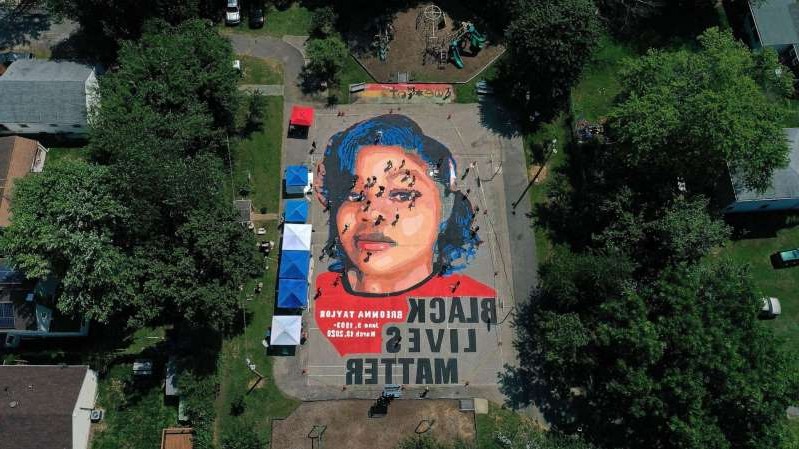 a sign in front of a tree: In an aerial view from a drone, a large-scale ground mural depicting Breonna Taylor with the text 'Black Lives Matter' is seen being painted at Chambers Park on July 5, 2020, in Annapolis, Md.