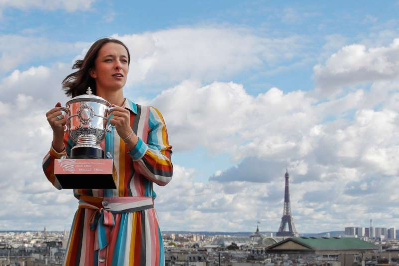 The Eiffel Tower is seen in the background, as Poland's Iga Swiatek, suddenly becoming a Grand Slam champion at the age of 19, poses with her trophy during a photo call on the rooftop of Galeries Lafayette, Sunday, Oct. 11, 2020, after winning the final match of the French Open tennis tournament at the Roland Garros stadium in Paris, France, Saturday. (AP Photo/Christophe Ena)