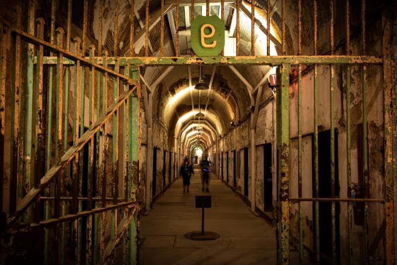 a building with a metal fence: This is inside the Eastern State Penitentiary in downtown Philadelphia. The attraction has canceled its annual