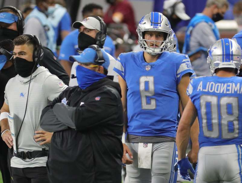 a group of people standing in front of a crowd: Detroit Lions quarterback Matthew Stafford (9) and head coach Matt Patricia watch a score by the New Orleans Saints during the second half Sunday, October 4, 2020 at Ford Field.
