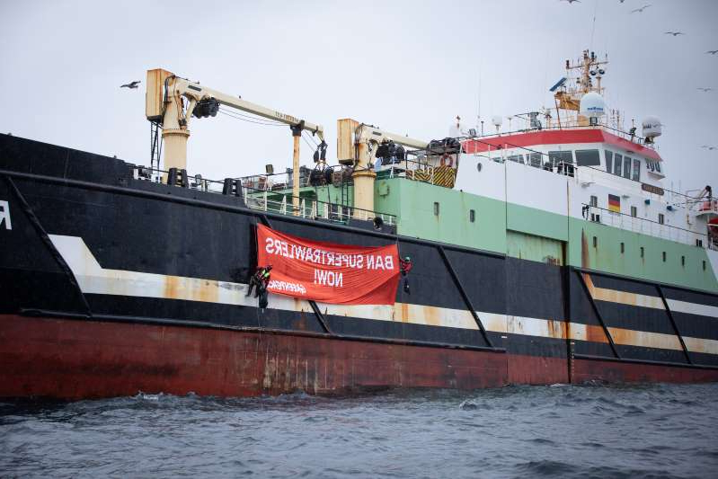 a large ship in a body of water: Two Greenpeace UK activists unfurl on the Helen Mary a banner reading 'Ban Supertrawlers Now!' (Greenpeace/PA)