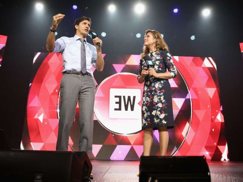 Justin Trudeau standing in front of a stage: Sophie Gregoire Trudeau, left, and Prime Minister Justin Trudeau speak on stage at a WE Charity event in New York in 2017.