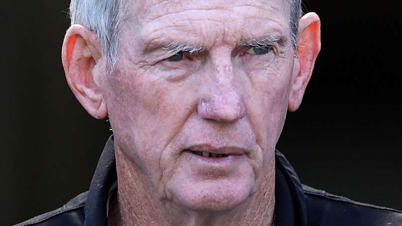 a close up of Wayne Bennett wearing glasses and smiling at the camera: Wayne Bennett.