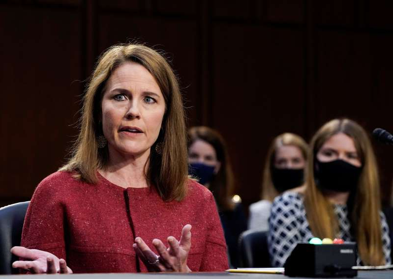 a man and a woman looking at the camera: Supreme Court nominee Judge Amy Coney Barrett participates in the second day of her confirmation hearing before the Senate Judiciary Committee on Capitol Hill in Washington, D.C., on Oct. 13.