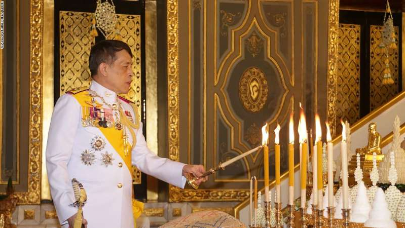 a man standing in front of a cake: Thailand's King Maha Vajiralongkorn lights candles as he takes part in a Buddhist ceremony to mark the 2020 Kathina festival at Wat Ratchabophit in Bangkok on October 10, 2020.