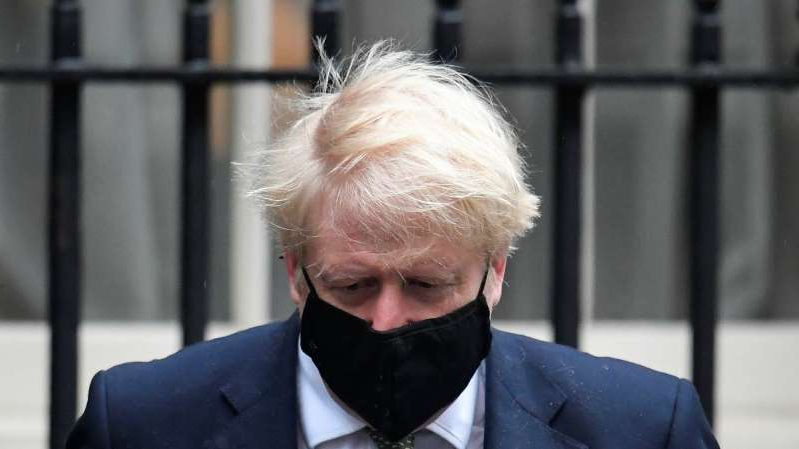 a man wearing a suit and tie: Boris Johnson is under growing pressure to take greater action to slow the spread of COVID-19