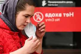 A woman takes off her face mask outside a metro station in Moscow on Tuesday. Amid record daily new coronavirus cases, officials are resisting a second lockdown and instead are stepping up enforcement of health precautions.