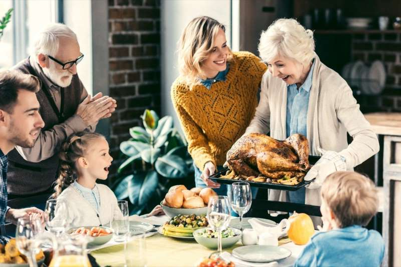 a group of people sitting at a table: grandmother carrying turkey for family on thanksgiving dinner