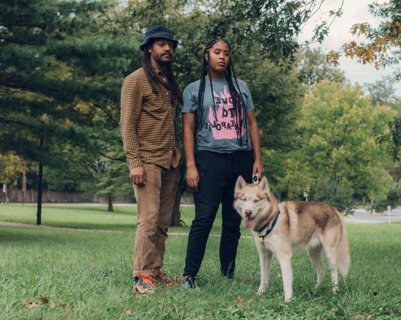 a person holding a dog on a leash standing on grass: Ayanna Brooks and her boyfriend, Joseph Burroughs, were walking her dog in their Washington, D.C., neighborhood when a dog from a Maryland K-9 unit bit her. (Photo by Jared Soares for The Marshall Project )