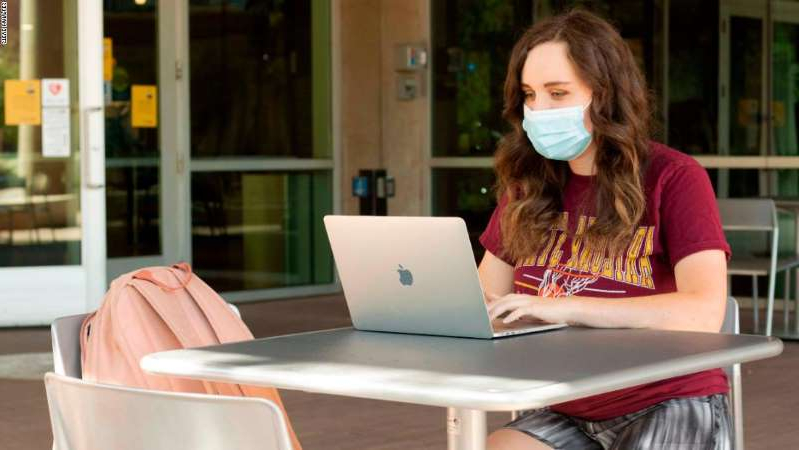 a person sitting at a table using a laptop: At Arizona State University, students are allowed to participate in in-person classes as long as they wear a mask and socially distance from one another.