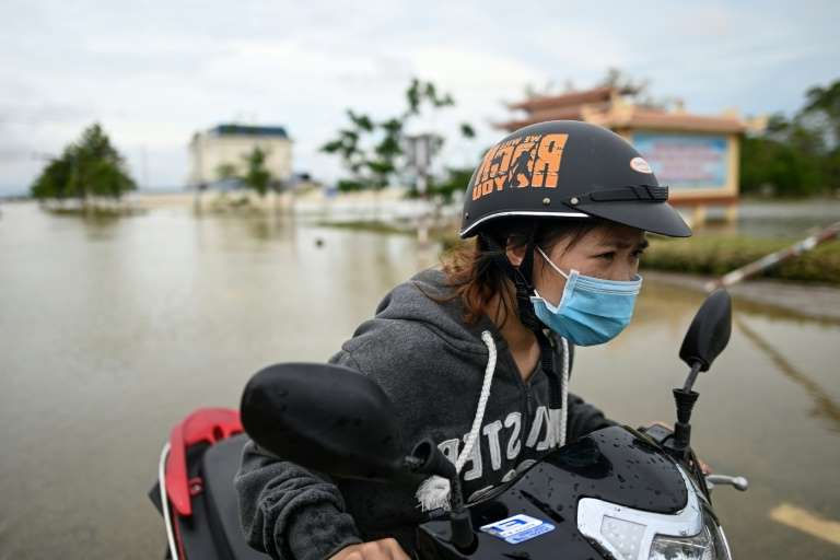 a person wearing a helmet: A woman pushes her scooter along a flooded road in Quang Dien district in central Vietnam's Hue province