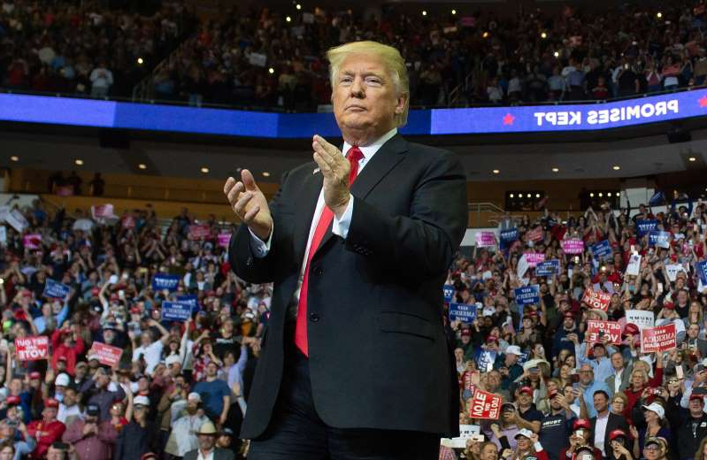 "Donald Trump standing in front of a crowd: President Donald Trump arrives for a campaign rally at the Toyota Center in Houston, Texas, on October 22, 2018. A billboard showing support for the president in the Houston has been defaced to read ""take Trump to prison."""