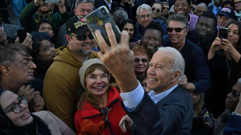 Joe Biden, koby Maxwell standing in front of a crowd posing for the camera: Joe Biden taking a selfie with supporters at a rally in Virginia on Election Day in 2019.