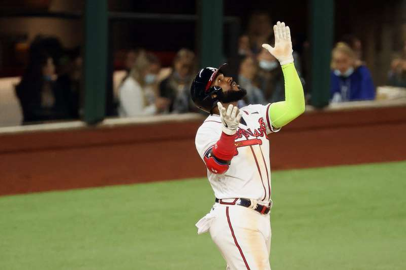 a baseball player holding a bat on a field: Marcell Ozuna went 4-for-5 in Game 4 of the NLCS against the Dodgers.