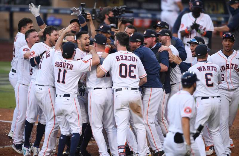 a group of baseball players that are standing in front of a crowd: Astros players celebrate Carlos Correa's walk-off home run in Game 5.