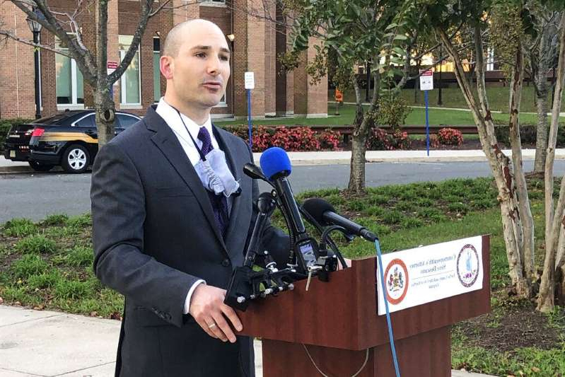 a man wearing a suit and tie walking on a sidewalk: Fairfax County Commonwealth's Attorney Steve Descano announces charges against two federal police officers.