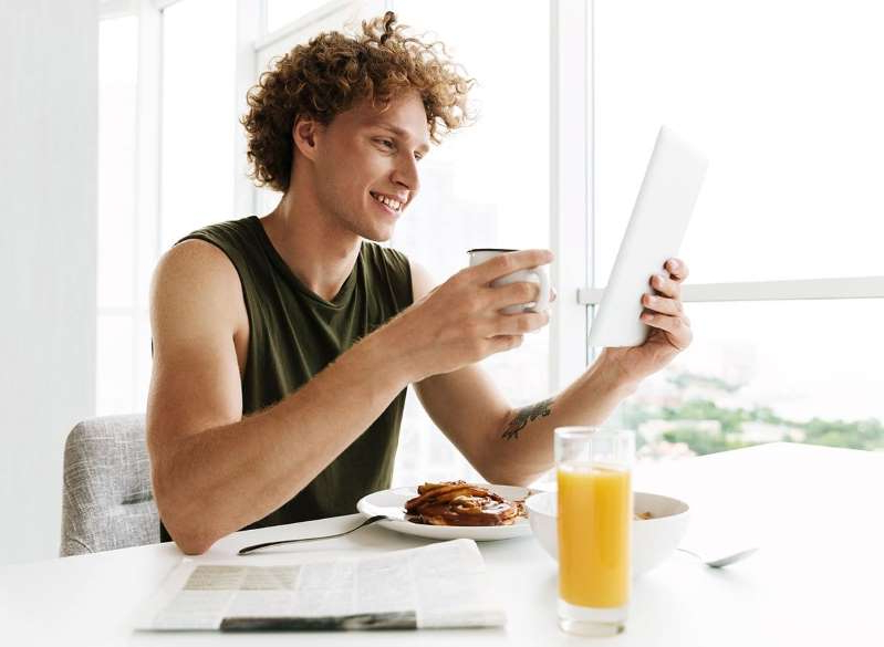 a person holding a plate of food: man eating breakfast