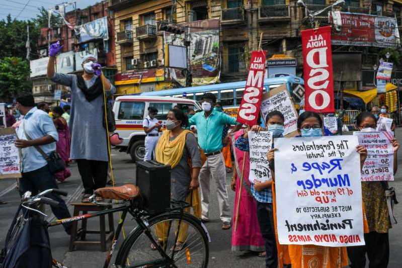 a person riding a bicycle on a city street: A protest in Kolkata against the alleged rape, torture and murder of a 19-year-old Dalit woman in Hathras district of Uttar Pradesh, India.