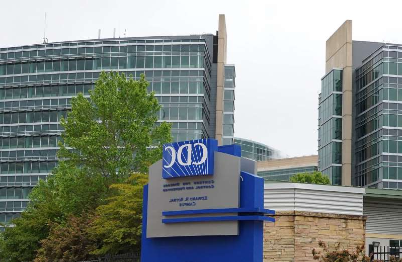 a sign in front of a tall building in a city: In this file photo taken on April 24, 2020, shows the Centers for Disease Control (CDC) headquarters in Atlanta, Georgia.