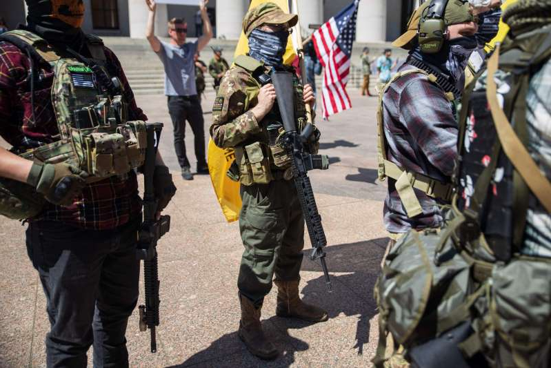 a group of people in uniform: (File photo) A local militia group is seen at a rally to protest the stay-at-home order amid the Coronavirus pandemic in Columbus, Ohio on April 20, 2020. The sheriff of Kenosha is telling armed militia groups to stay away from polling places in November.