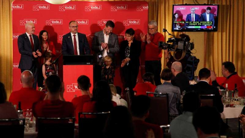 a group of people sitting at a table in front of a crowd: Andrew Barr celebrates a Labor victory with family and party faithful at the Belconnen Labor Club. (ABC News: Ian Cutmore)