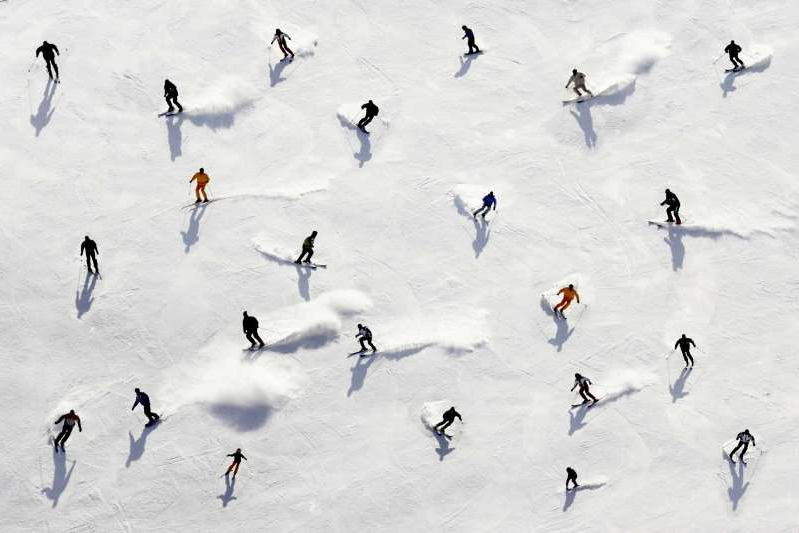 a group of people skiing down a snowy hill: Getty Images